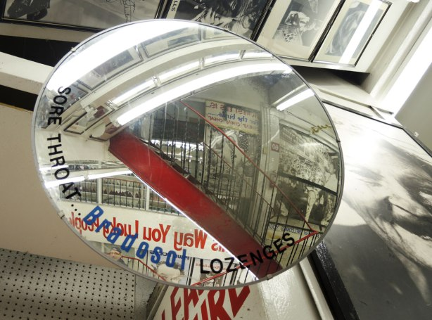 reflections in a round mirror in a staircase at Honest Eds store showing the stairs, railing and various pictures and posters hanging on the walls