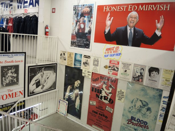 movie posters as well as other kinds of posters in a stairwell at Honest Eds, including a large red poster with a picture of 'Honest Ed Mirvish'.