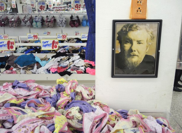 bins of panties for sale, a wall display and long horizontal mirror in the background.  Beside the bin in the foreground is a white pillar on which there is a black and white picture of a man from the shoulders up.