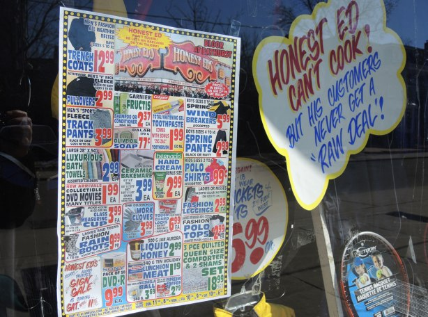 "Signs in a store window.  One says ""Honet Ed can't cook but his customers never get a raw deal"" and the other is a page showing all the special prices available at the store.  It is printed like a newspaper page and there is a lot of information on it."