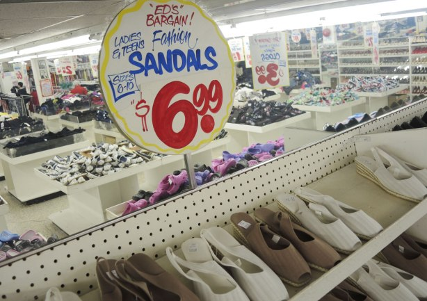 Sandals for sale at Honest Eds, on white shelves.  There is a mirror behind and in the reflection is most of the shoe department of the store.