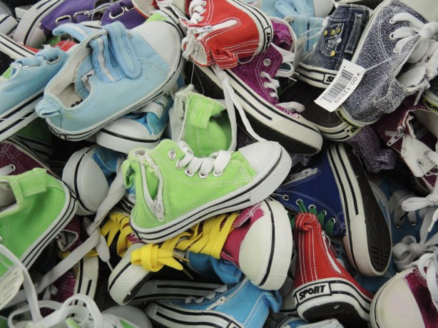 A bin full of brightly coloured kids running shoes in greens, blues, reds, etc