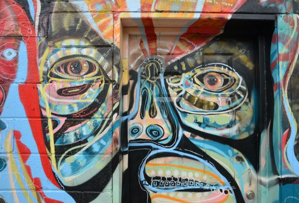 Close up of a stylized and slightly abstacted man's face on a wall in an alley