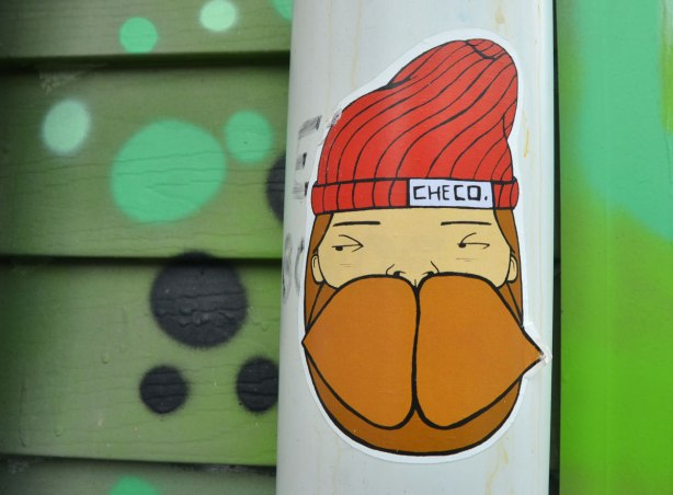 A sticker on a pole with green in the background. The sticker is of a man's head. He has a beard and big brown moustache and he is wearing a red toque with a label on it that says 'checo'