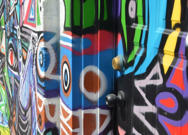 Close up, and a side angle shot, of colourful graffiti on a door, door frame and wall.  Bright colours, geometric shapes such as white circle around brown, pink zig zags.