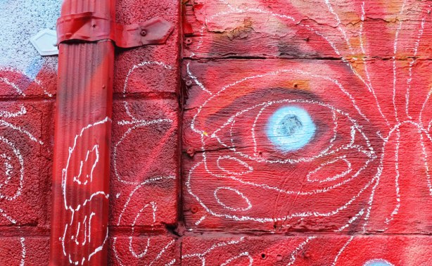 close up of a street piece that is very red, with one whitish grey eye.  Some faint swirly white lines demark the face, or at least the upper quadrant that is visible in the picture