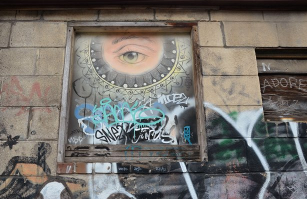 One very realistic eye in a partial circle, in a boarded up window above head level so it looks like it's looking down at you.