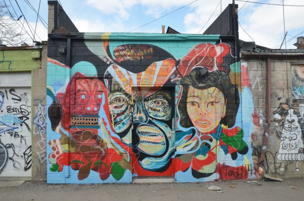 A wall with a door in the middle of it.  There is a street art piece of three heads.  Two very stylized men and a more realistic looking woman.  Bright colours.