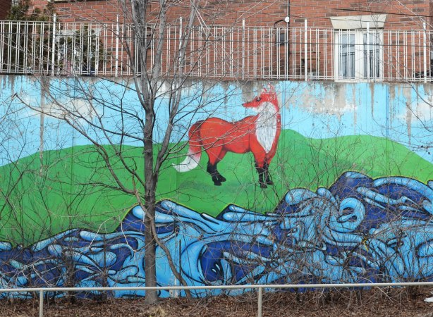Part of a mural showing a fox standing beside a creek.  A bare tree is in front of the mural