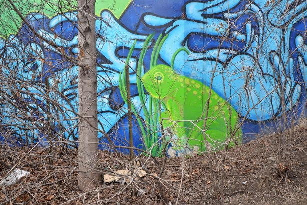 Part of a mural showing a large green frog sitting beside a creek.  A tree with no leaves is in front of the mural