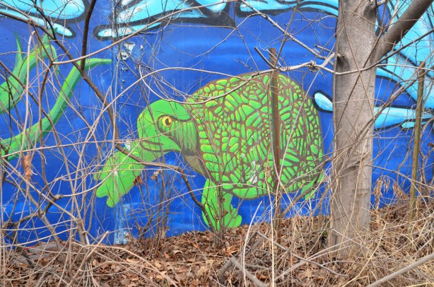 Part of a mural showing a large green turtle swimming in a creek.  A tree with no leaves is in front of the mural