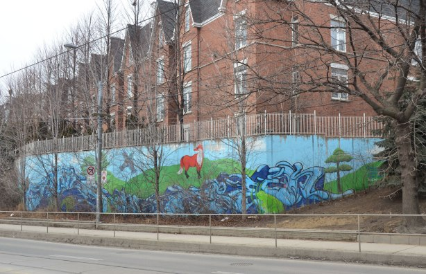 A mural is painted on a retaining wall at the bottom of a small hill that separates some row houses and the street.  Many small trees are in front of the mural but it is winter time so there are no leaves on the trees.  The mural is a stylized creek that flows through hills with some animals standing beside it - fox, frog, turtle and beaver.