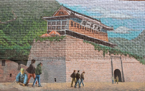 part of large mural of the great wall of China in an alley, painting of a few people walking towards a building on the great wall