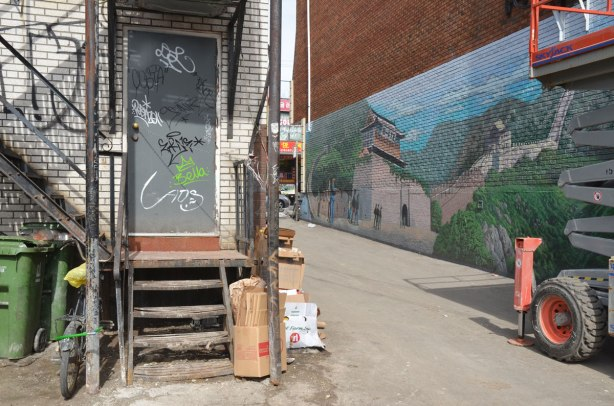 part large mural of the great wall of China in an alley, the street end of the alley with part of the mural, the back door of a shop on the other side of the alley is also in view