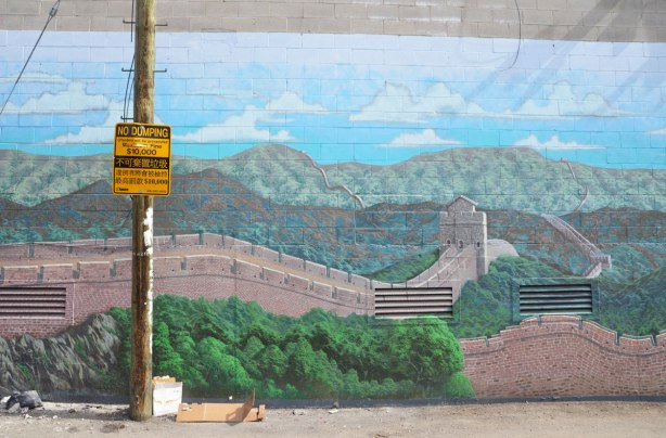 part of large mural of the great wall of China in an alley with a telephone pole in front of it.