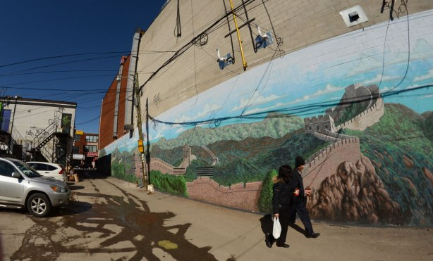 large mural of the great wall of China in an alley, wide angle view with two people walking in front of it
