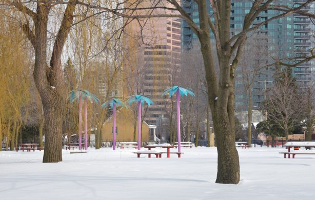 A park in winter with some large trees including a willow tree.  Some picnic benches are covered in snow, there are apartment buildings in the background.  There are also 5 fake palm trees with tall skinny magenta trucks and bright blue, almost turquoise, palms.  Art in the park.