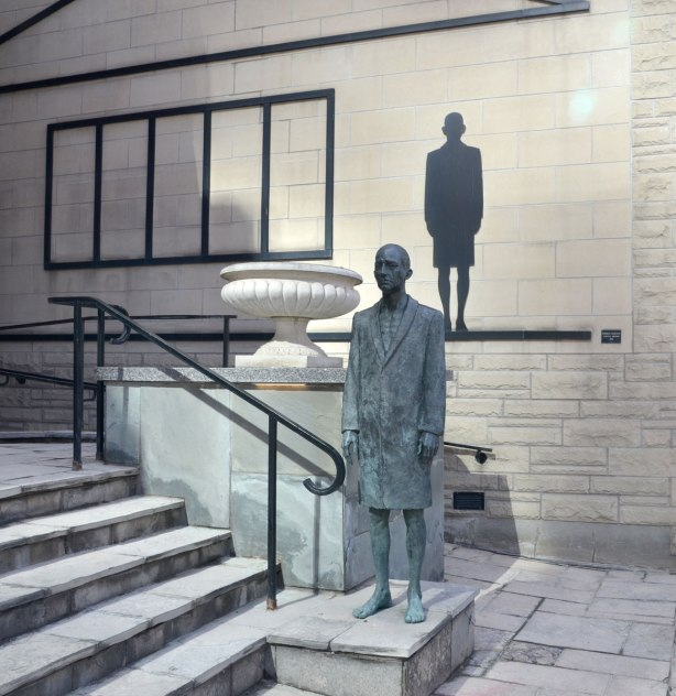 A bronze sculpture of a man in bare feet.   He is wearing an overcoat.  He is standing with his arms passively at his side.   Behind him on a wall is a black silhouette that looks like his shadow.  A large white planter is also in the picture although there is nothing growing in it.