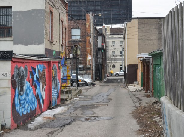 looking west along an alley in late winter.  Street art on the walls on the left, garage doors on the right.  Buildings on Roncesvalles can be seen at the end of the alley which is about a block long.