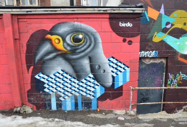 a mural by birdo, a small black and grey bird that is holding a geometric shape in blue and white diamond shaped sections.