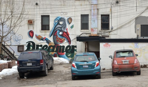 "A birdo mural on a dirty light grey wall of a stylized bird and the word ""dreamer"" written in large black letters."