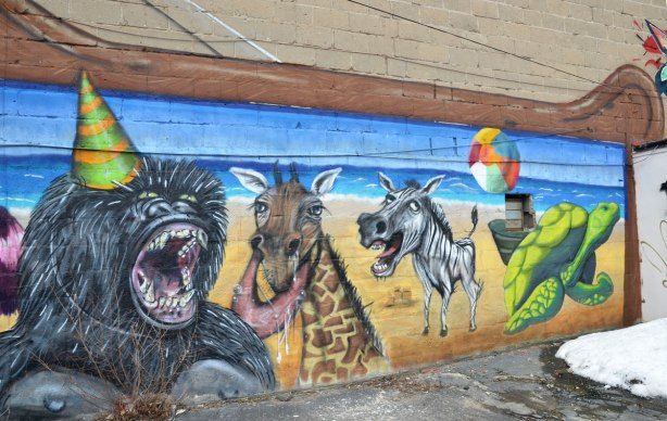 Destination Mammals Cabana mural, middle part, large baboon wearing a party hat, a giraffe, a crazy looking zebra and a green turtle, street art on a wall.