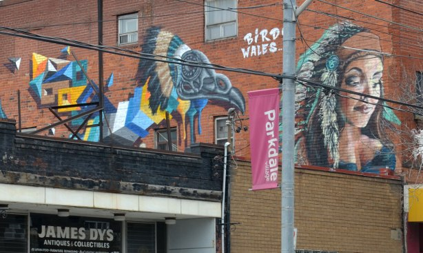 "Close up of Two pieces of street art along the upper floor of a brick building.  In front, closest to the street is a young woman's head.  The other is a colourful stylized bird by the street artist Birdo.  The words ""Birdo Wales"" are written in white letter between the two pieces."