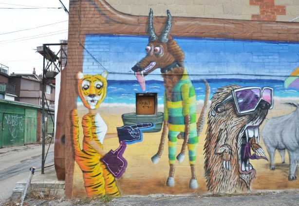 Destination Mammals Cabana mural,  upright yellow tiger, antelope wearing yellow and green stripe beach wear and some other hairy creature with sunglasses on.