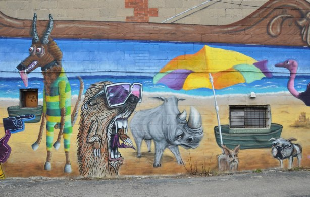 Destination Mammals Cabana mural, hairy creature with mouth wide open and wearing suglasses and a rhino by a beach umbrella, street art, graffiti,
