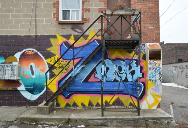 metal stairs to a small landing outside a door on the second storey of a concrete brick building.  The walls of the bottom floor are covered with graffiti.  Immediately behind the stairs is a large blue letter Z.