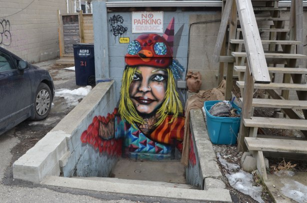 A street art piece painted in a small stairwell, down from alley level.  The door way is the head of a woman and her arms extend over part of the stairwell walls.  She is dressed in red and blue including a birdo hat.
