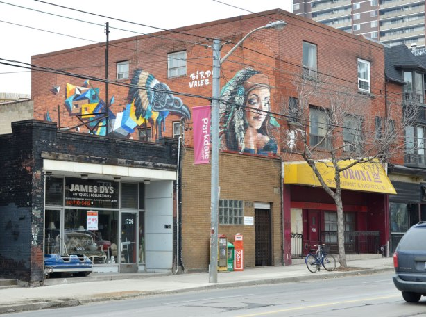 "Two pieces of street art along the upper floor of a brick building.  In front, closest to the street is a young woman's head.  The other is a colourful stylized bird by the street artist Birdo.  The words ""Birdo Wales"" are written in white letter between the two pieces.  The Corona Restaurant with a yellow awning is on the right and James Dys Antiques and Collectibles is on the left.  is on the left."