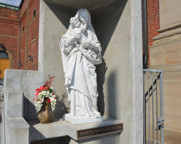 White statue of Mary and Jesus outside a church, a vase of red and white flowers is beside her feet. The words Sancta Maria Mater Dei are on a bronze plaque under the statue.
