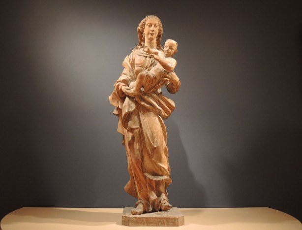 Wooden statue of Mary standing while holding a baby Jesus.