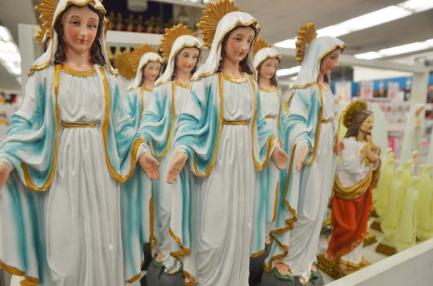 seven figurines of Mary painted with long white, light blue and gold robes. They are about 20 cm high, all with downcast eyes except the one on the left looks like she's looking at the camera.