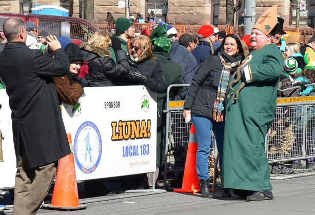 A heavyset man wearing long green robe and carrying a plastic snake.  He is supposed to be St. patrick, the patron saint of Ireland who drove the snakes out of Ireland many centuries ago.