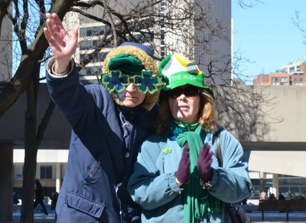 A couple watching a St. Patricks Day parade.  He is wearing big shamrock shaped glasses.  They are both wearing green hats.  He is waving to the camera.