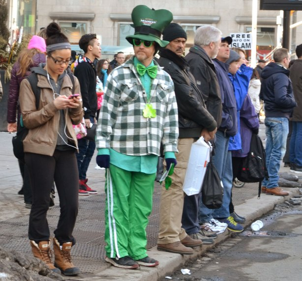 A man dressed in green, green pants, green shirt, big green bowtie, green shunglasses, and a big green hat, and he's wearing a shamrock around his neck.