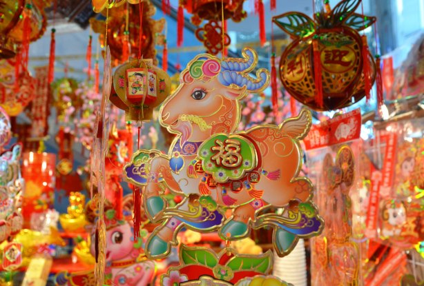 hanging paper decorations for Chinese New Year in bright colours and featuring ram and sheep shapes.