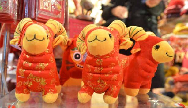 Three little stuffed rams with smiling faces on a shelf in a store.  They are red and gold and look like they are wearing traditional Chinese clothes.