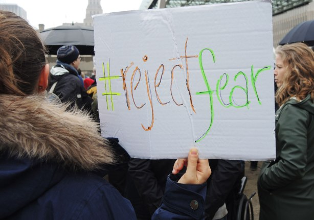 A protester is holding a hand written sign that says #rejectfear