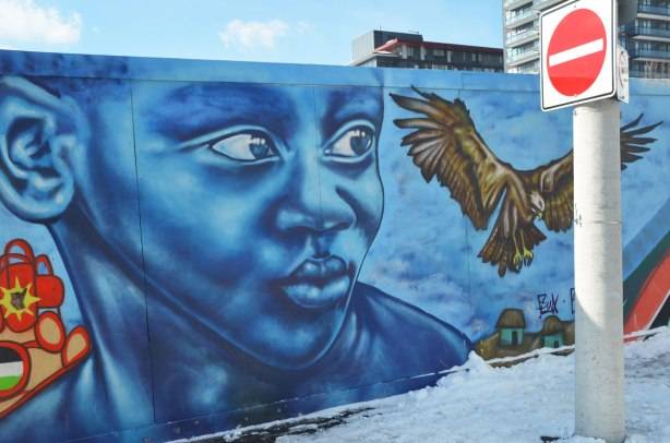 Colourful graffiti on hoardings around a construction site.  Large blue boy's face with a large bird taking flight beside him