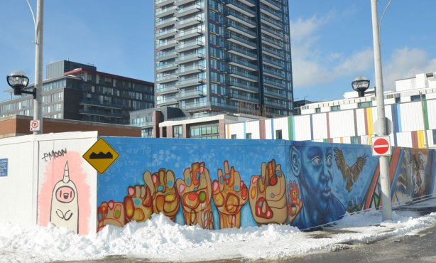 Colourful graffiti on hoardings around a construction site.  Six stylized hands in a row, on blue background.  Highrise apartment building is in the background.