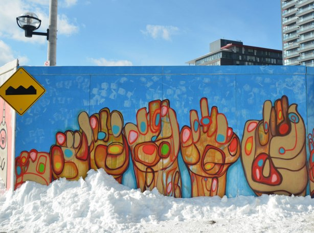 Street art of six stylized hands on a blue background.