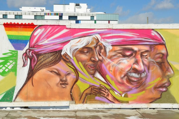 Colourful graffiti on hoardings around a construction site. A woman's head and three men's faces in profile.  They are all under the same pink head covering.