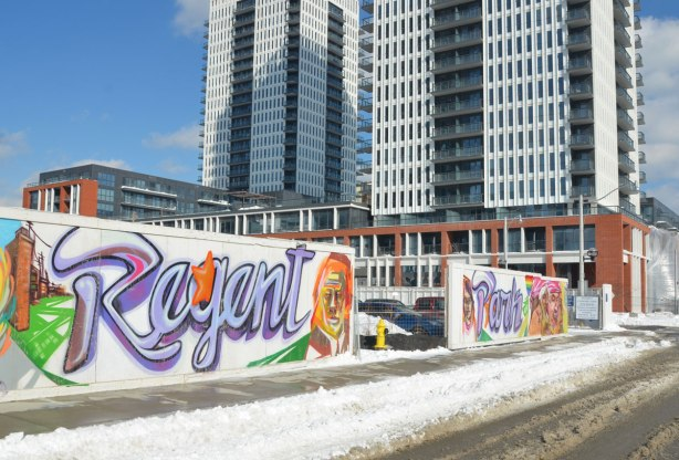 Colourful graffiti on hoardings around a construction site.  The words Regent Park are written in large blue  & purple cursive writing.  An entrance to the construction site is between the two words.