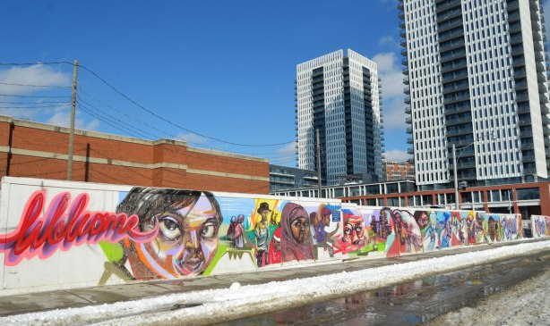 Colourful graffiti on hoardings around a construction site.  Scenes of people and faces, kids on bikes, activities.  The word Welcome is written in red cursive.  Two apartment buildings are in thebackground.