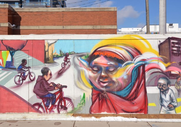 Colourful graffiti on hoardings around a construction site.  A large woman in head scarf with her eyes closed, people on bikes riding on a path