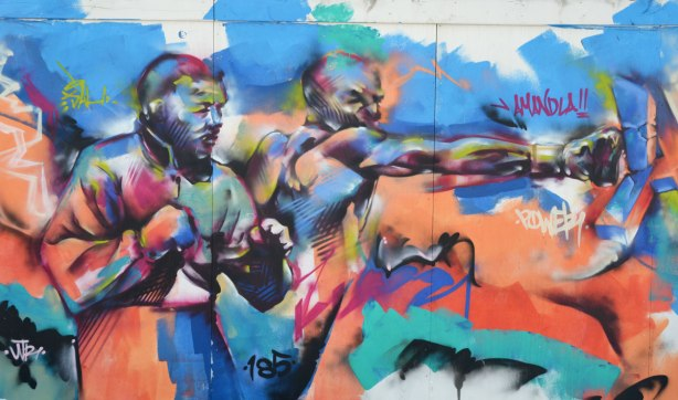 Colourful graffiti on hoardings around a construction site.  Two men punching, one is punching while the other stands beside him with fists clenched