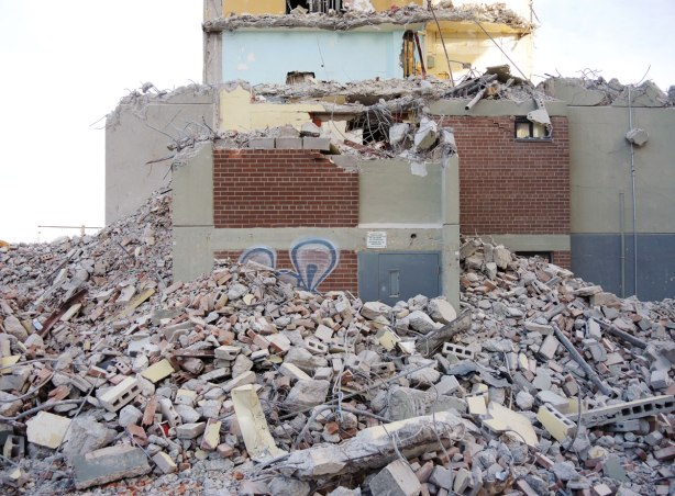 A lot of rubble, concrete, metal and brick, from the demolition of a building lies in front of the partially demolished building.